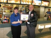 Russell Scott presents Tracy Voth of McDonalds Restaurant the 1,000th Food Safety 1st certificate.